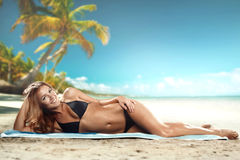 Girl lying on the beach. With palms on background Royalty Free Stock Image