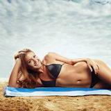 Girl lying on the beach Stock Image