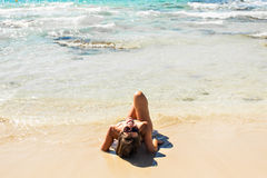Girl lying on the beach, sunbathing and relaxing. Summer journey to sea. Stock Photos