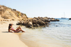 Girl lying on the beach, sunbathing and relaxing. Summer journey to sea. Royalty Free Stock Image