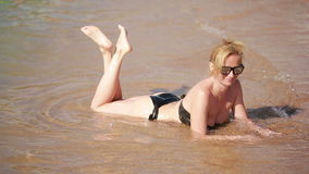 Girl lying on the beach in water. summer rest stock footage