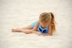 Girl Playing in Sand on Beach royalty free stock images