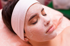 Girl lying in beauty spa with cosmetic facial mask on her face Royalty Free Stock Photos