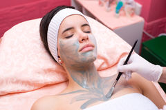 Girl lying in the beauty spa while facial mask is put on her face Royalty Free Stock Image
