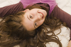 Girl lying in bed. A young girl lying in bed playing Stock Photos