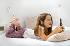 Girl lying on bed with cell phone. Little girl on bed with cell phone Stock Photo