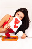 Girl lying in bed with gifts, cards, hearts, coff Royalty Free Stock Image