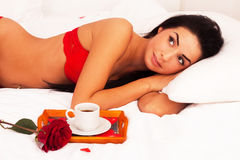Girl lying in bed with gifts, cards, hearts, coff Stock Photo