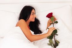 Girl lying in bed with gifts, roses, woke up, asle Stock Photography