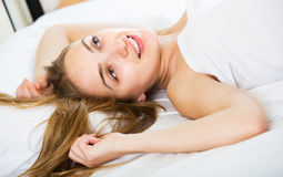 Girl lying in bed. Happy young girl lying in bed with opened eyes and smiling royalty free stock photos