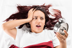 A girl lying on a bed and holding her head looking at the alarm clock realizing that she is late Stock Images