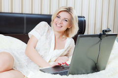 Girl lying in bed with laptop Royalty Free Stock Image