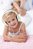 Girl lying in bed listening to the music Royalty Free Stock Photography