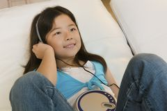 Girl lying in bed Listening to Music on CD Player close up Royalty Free Stock Photo