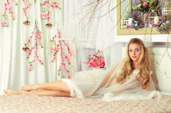 Girl. Lying on the bed in a negligee among the flowers Royalty Free Stock Photo