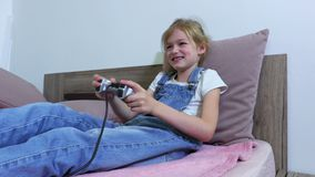 Girl lying in bed and play computer game stock video footage
