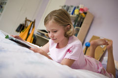 Girl (6-8) lying on bed, reading book, side view, surface level (tilt) stock photography