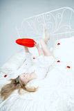 Girl lying on the bed with a red heart Stock Image