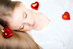 Girl lying on the bed with a red heart Stock Photos