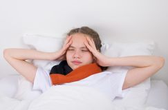 Girl lying in bed with a sore throat holding her hands royalty free stock images