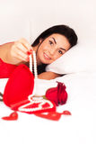 Girl lying in bed, strewn with hearts and roses Royalty Free Stock Image