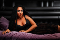The girl is lying on the bed. Stylish hairstyle, dreadlocks. Black lady. nightfall. Girl with an unusual hairdo. Black long hair. dreadlocks Stock Photography