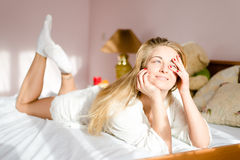 Girl lying in bed in the sunlight & happy smiling Royalty Free Stock Image