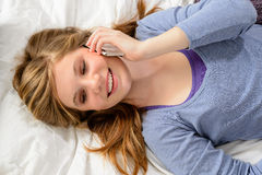 Girl lying in bed talking on phone Stock Photo