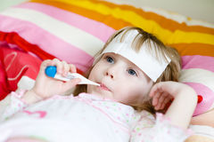 Girl lying in bed with a thermometer Royalty Free Stock Images