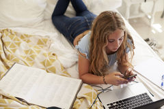 Girl lying on bed using smartphone and laptop, high angle Royalty Free Stock Images