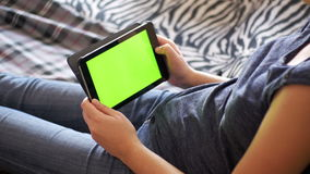Girl lying on bed and using tablet with green screen at home. Girl Lying on Bed and using Tablet with Pre-Keyed Green Screen at Home. Woman hands using digital stock video footage