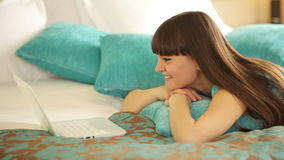 Girl lying on bed and watching something on laptop stock video footage