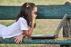 Girl lying on a bench with computer Stock Images