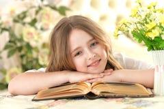 Girl lying on big opened book Royalty Free Stock Photography