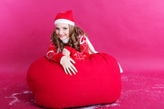 Girl is lying on big red christmas bag Stock Photos