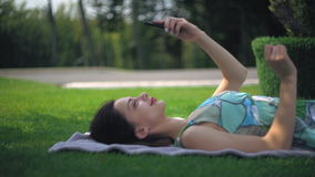 Girl lying on blankets and typing message on the phone. Woman rest in the park using mobile phone. Caucasian happy female chatting on smartphone using internet stock video footage