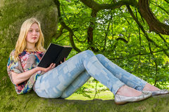 Girl lying on branch of tree reading book Royalty Free Stock Image