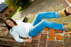 Girl lying on brick banisters. Girl lies on the wide brick banisters of the old building royalty free stock images
