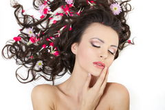 Girl lying with bright red flowers in her hair Royalty Free Stock Image