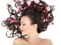 Girl lying with bright red flowers in her hair Royalty Free Stock Images