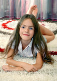 Girl lying on a carpet Stock Images