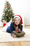 The girl lying on the carpet with a gift Royalty Free Stock Photos