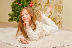 Girl lying on the carpet, looking at the camera and smiling. Stock Photos