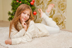 Girl lying on the carpet, looking at the camera and smiling. Stock Images