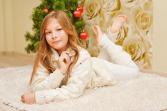 Girl lying on the carpet, looking at the camera and smiling. Royalty Free Stock Image