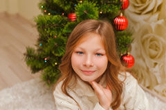 Girl lying on the carpet, looking at the camera and smiling. Royalty Free Stock Photos