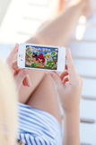 girl lying on a chaise lounge holding iPhone with game Angry Birds on the screen royalty free stock images