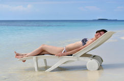 Girl lying on a chaise lounge. On the ocean beach royalty free stock images