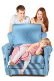 Girl is lying on char. father and mother behind Stock Image