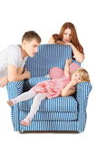 Girl is lying on char. father and mother near Stock Photos